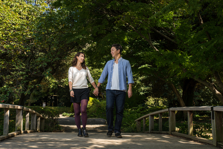 Beautiful asian couple dating in a park - Japanese man and woman having fun outdoors Stock Photo