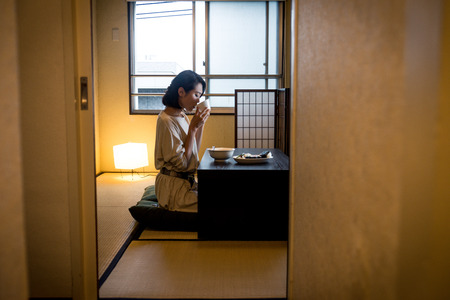 Asian woman eating in a traditional japanese apartment in Tokyo