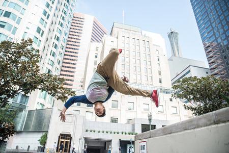 Parkour-Mann macht Tricks auf der Straße - Freiläufer, der seinen akrobatischen Hafen im Freien trainiert