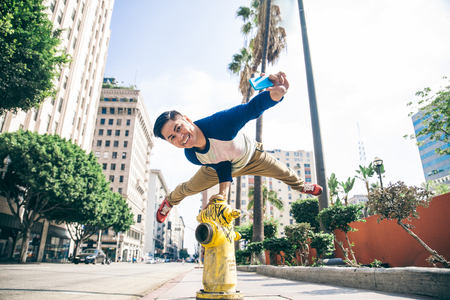 Parkour man doing tricks on the street - Free runner training his acrobatic port outdoors and taking a picture Stock Photo