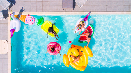 Happy people partying in an exclusive swimming pool with animal and fruit shapes mats, view from above Stockfoto - 102316682