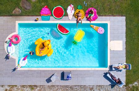 Gente feliz de fiesta en una piscina exclusiva con esteras de formas de animales y frutas, vista desde arriba Foto de archivo