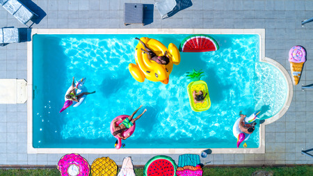 Happy people partying in an exclusive swimming pool with animal and fruit shapes mats, view from above Stockfoto - 102311753