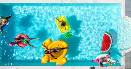 快乐的人们在一个有动物和水果形状的垫子的专属游泳池里聚会,从上面看