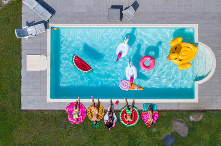 Happy people partying in an exclusive swimming pool with animal and fruit shapes mats, view from above Stockfoto - 102311793