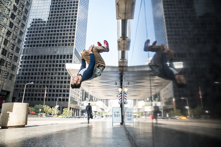 Parkour man doing tricks on the street - Free runner training his acrobatic port outdoors