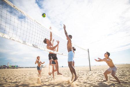 Gruppe von Freunden, die Beachvolleyball spielen - Multi-ethische Gruppe von Menschen, die Spaß am Strand haben