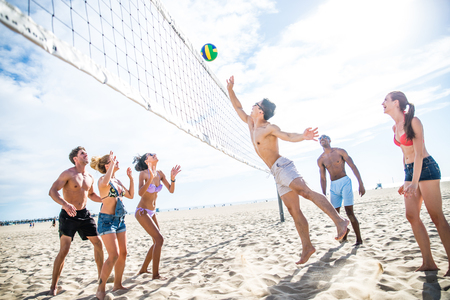 Group of friends playing beach volley - Multi-ethic group of people having fun on the beach Banque d'images - 102291710