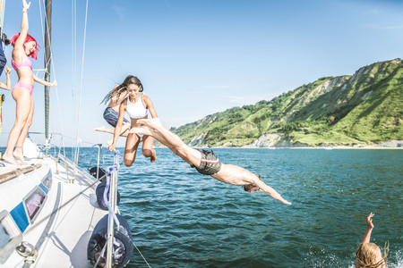 Multiethnic group of friends sailing on a boat - Summer holidays, young adults having fun Stock Photo