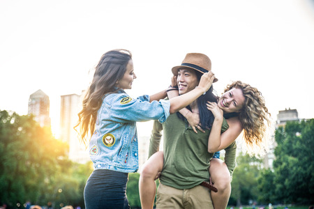 Multi-ethnic group of friends in Central Park, Manhattan - Young cheerful people bonding outdoors