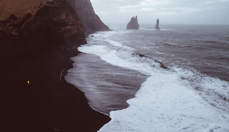 Black sand beach, and basaltic rocks in the ocean in Iceland Stockfoto