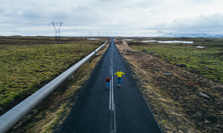 Couple of skateboarders on the icelandic roads Banco de Imagens
