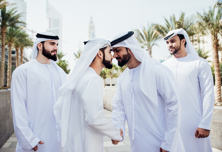 Group of businessmen talking on the street in Dubai Stock Photo