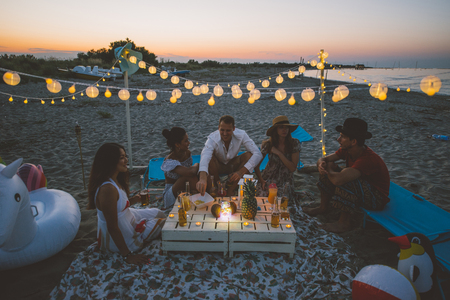 Groupe d'amis faisant la fête sur la plage au coucher du soleil Banque d'images