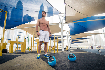 Young athletic man training outdoors - Young adult doing a fitness workout