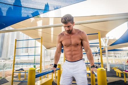 Junger athletischer Mann, der draußen trainiert - junger Erwachsener, der ein Fitness-Training macht Standard-Bild