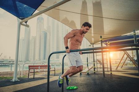 Junger athletischer Mann, der draußen trainiert - junger Erwachsener, der ein Fitness-Training macht
