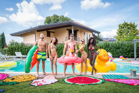 Multiracial group of friends having party in a private villa with swimming pool - Happy young people chilling with shaped air mattresses Standard-Bild - 105547442