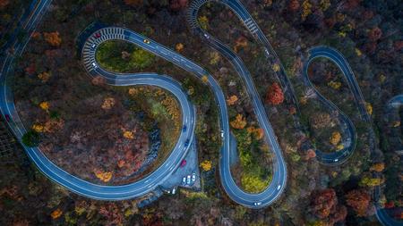 Narrow street between woodland, drones view - Irohazaki winding road, Nikko Stockfoto