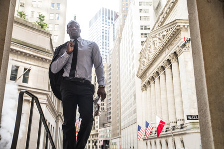 Businessman in full suit walking in Wall Street, New York Stock Photo