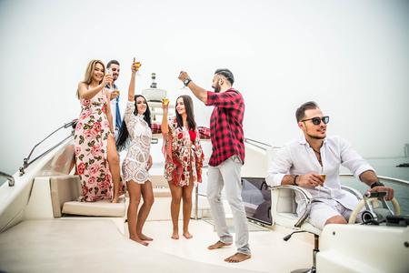 Grupa przyjaciół podejmowania strony na jachcie w Dubaju - szczęśliwi ludzie mający fantazyjne przyjęcie na luksusowej łodzi