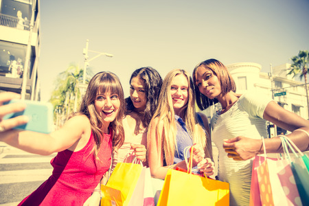Multiethnic group of girls shopping - Four beautiful woman having fun while buying some presents in a mall in Beverly Hills