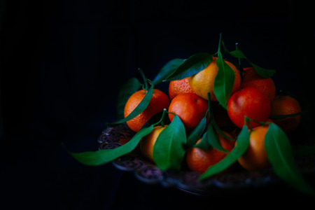 Tangerines with leaves  on a vintage plate
