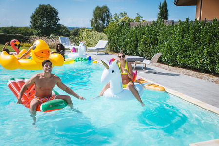 Multiracial group of friends having party in a private villa with swimming pool - Happy young people chilling with shaped air mattresses Stockfoto - 105387221