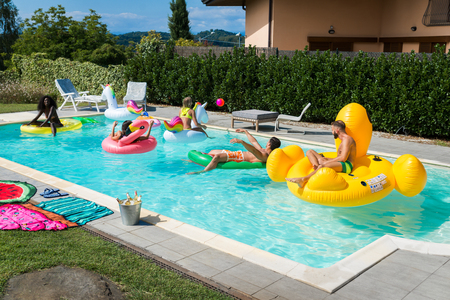 多种族的朋友群有一个私人别墅的游泳池-快乐的年轻人冷却与形状的气垫