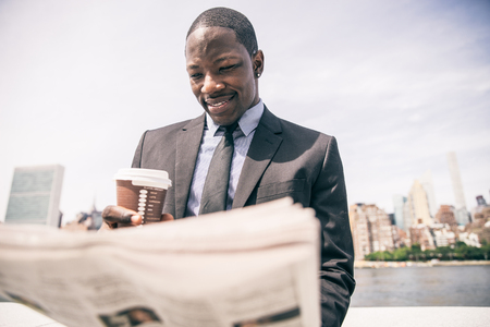 Confident businessman. Successful young man in full suit reading financial news on newspaper and drinking a cup of coffee Foto de archivo