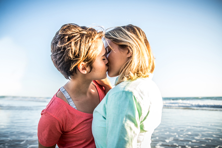 Lesbian couple kissing on the beach Stockfoto