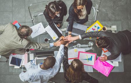 Equipo de hombres de negocios que se unen durante una reunión exitosa: CEO y gerentes en la oficina de una empresa, conceptos sobre el trabajo en equipo y la unidad, vista desde arriba