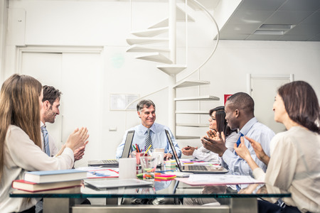 Business team having a meeting in a office, afro-american man exulting and his colleagues clapping hands - Successful businessman getting a promotion at work