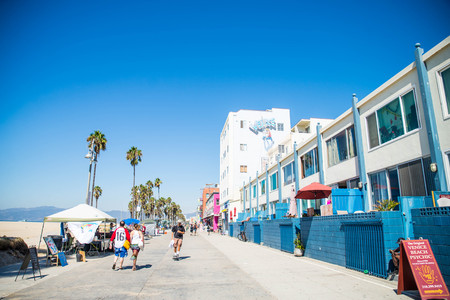 VENICE BEACH, USA - SEPTEMBER 29, 2016: The crowded Venice Beach Boardwalk. Lots of people are strolling down the boardwalk. On the sides there are several shops and palm trees. Stock Photo - 105773239