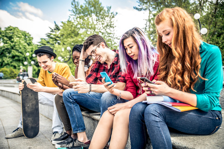Multiethnic group of friends looking down at phone and tablet - concepts about technology addiction and youth Stock Photo