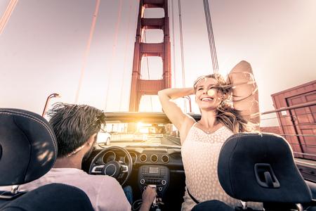 Couple of lovers driving on a convertible car - Newlywed pair on a romantic date, woman with outstretched arms on Golden Gate Bridge