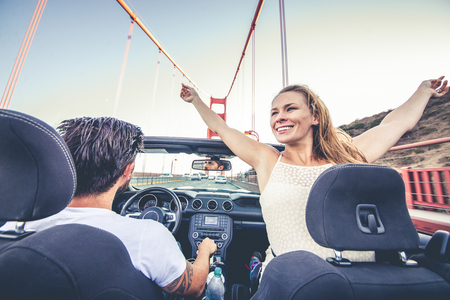Couple of lovers driving on a convertible car - Newlywed pair on a romantic date, woman with outstretched arms on Golden Gate Bridge Stockfoto - 106021202