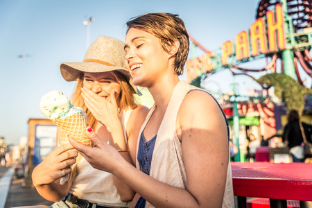 Two young women eating ice cream of Santa Monica pier and having fun