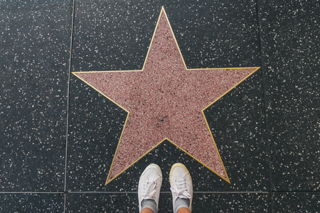 Tourist photographing her with an empty star on the Walk of Fame in Hollywood Imagens