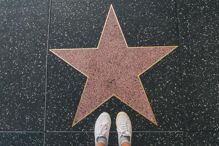 Touriste la photographiant avec une étoile vide sur le Walk of Fame à Hollywood