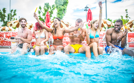 Multi-ethnic group of friends in a swimming pool - Young happy people having fun and enjoying summertime in a aquapark Stockfoto