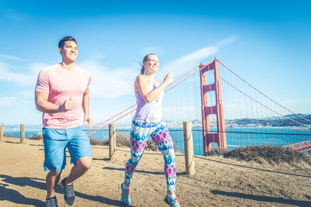 Couple running in San francisco. Golden gate bridge in the background - Sportive people training outdoors