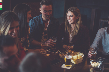 Group of teens having fun in a pub