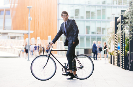 Handsome young business man with his modern bicycle.