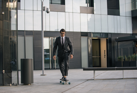 Handsome young business man with his modern longboard