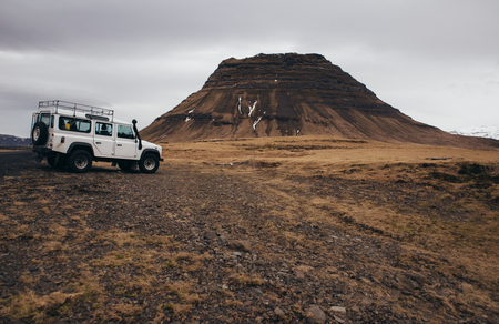 ICELAND, KIRKJUFELL, 16TH APRIL 2018. The land Rover defender parked in front the kirkjufell. The Defender is a four-wheel drive off-road vehicle developed in the 1980s Editorial