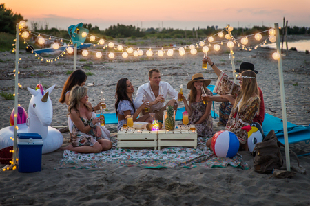 Group of friends having a picnic at the beach - Happy young people on a summer vacation at the beach Stock Photo