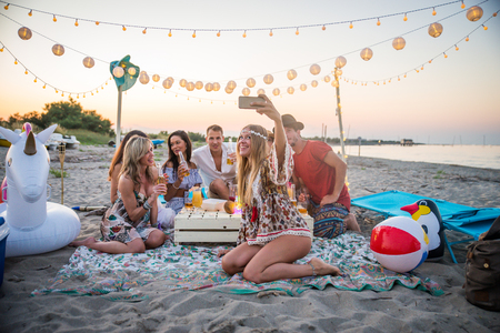 Group of friends having a picnic at the beach - Happy young people on a summer vacation at the beach Banco de Imagens