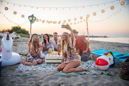 Gruppo di amici che hanno un picnic in spiaggia - Giovani felici in vacanza estiva in spiaggia