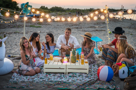 Group of friends having a picnic at the beach - Happy young people on a summer vacation at the beach Standard-Bild